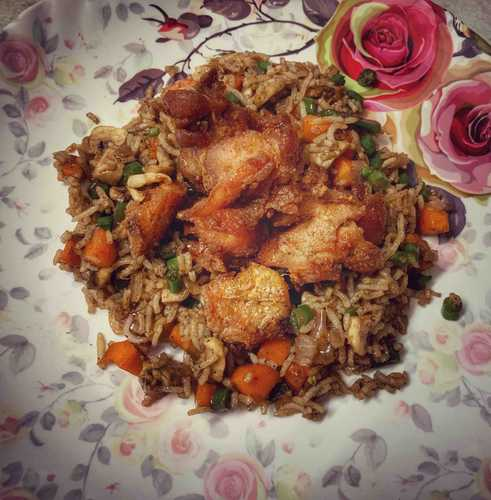 Mushroom fried rice with baked chicken thighs.