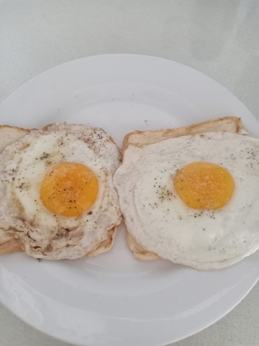 Half of a fried egg with bread