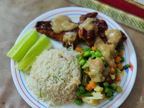 Chicken steak meal with garlic rice and stir fried vegetables -continental cuisine